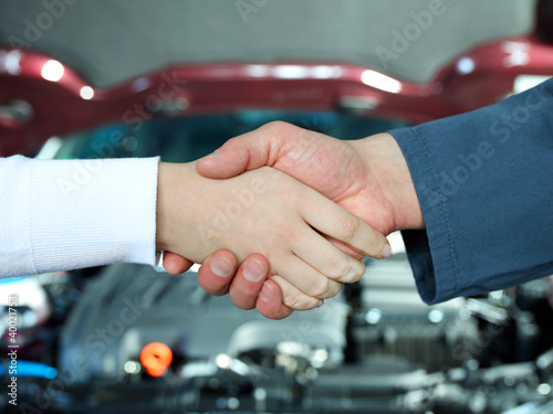 Female customer and master mechanic shaking hands in a garage