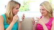 Two blonde women drinking coffee
