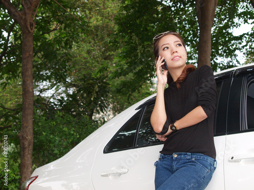 Young pretty Asian standing near car and calling by phone