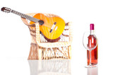 Rose wine bottle and glass with a guitar on background