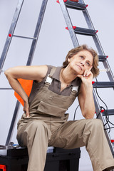Senior woman sitting in a toolbox