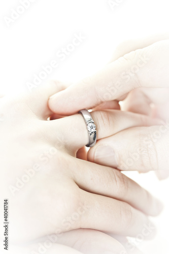Man putting engagement ring on finger