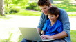 Boy on his father's tigh using a laptop