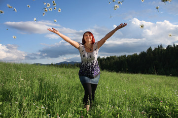 Happy young woman throwing daisy flowers