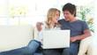 Joyful couple looking at a laptop