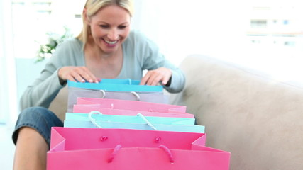 Happy woman looking into shopping bags