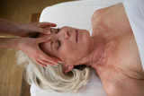 senior woman having a massage in a spa center