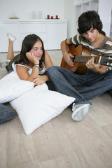 teenage lost in admiration for boyfriend playing guitar