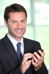 A smiling businessman about to make a phone call.