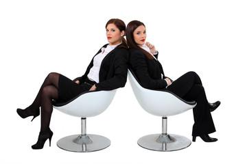 Two businesswomen sat in designer chairs