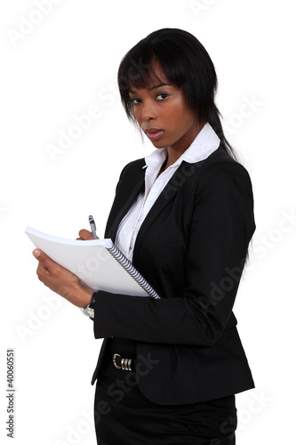 Office assistant writing notes on pad