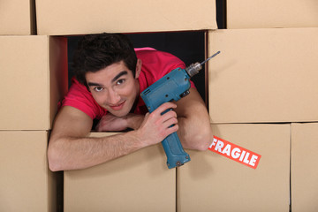 A man through a pile of cardboard boxes with a drill.