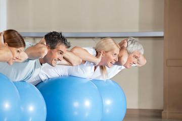 Senioren machen Liegestütze auf Gymnastikball