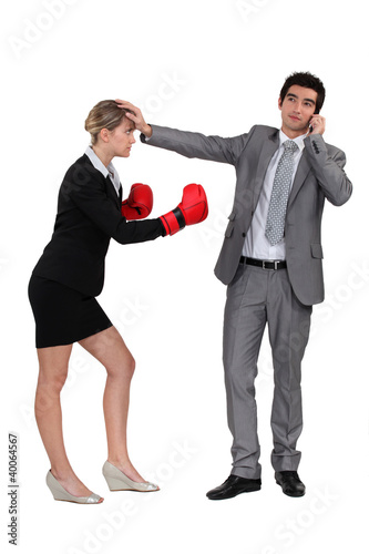 Businesswoman boxing on businessman on phone