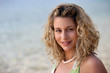 Curly-haired blond woman at the beach