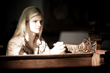 Blonde Woman Praying in a Church