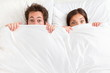 Funny surprised couple in bed
