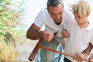 Father and son fishing with net
