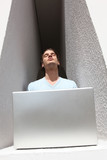 Man in an alcove basking in the sunshine whilst using a laptop