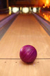 violet sphere ball standing on long bowling lane before strike