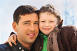 happy father and his little son wearing in jacket hug outdoor