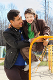happy father and little son wearing in jacket play at playground