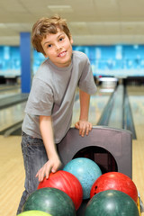 smiling happy boy stands near many balls in bowling club