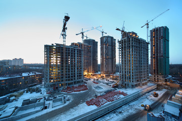 Seven high buildings under construction with cranes at day