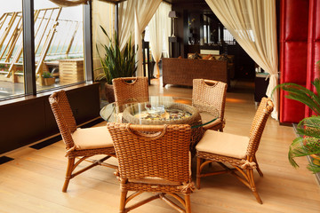 Beautiful wicker chairs and table in empty stylish restaurant