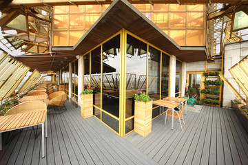 Wooden and wicker chairs and tables at terrace in restaurant