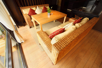 Two wicker couches with pillows and table in restaurant