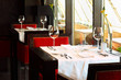 beautiful serving at tables with white tablecloth and red chairs