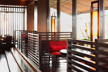 Row of brown tables and red seats in empty cozy restaurant