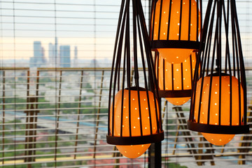Yellow lamp hanging from ceiling, outside window skyscrapers