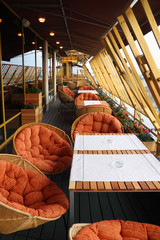 Row of origilal spherical wicker chairs and tables at terrace