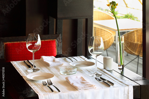 serving at table with tablecloth and chair in empty restaurant