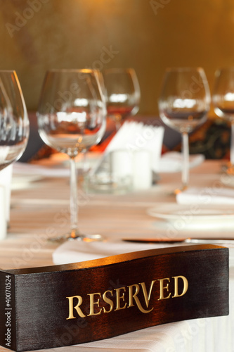 Wooden reserved plate on restaurant table with empty dishes