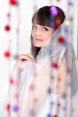 Smiling bride looks at camera behind transparent curtain