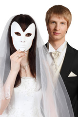 Beautiful bride hid face behind mask; groom stands behind