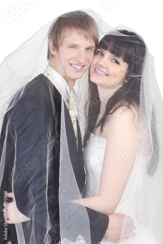 Happy young groom and bride hide under transparent veil isolated