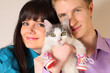 Fortunate young husband and wife hold cat wearing in boots