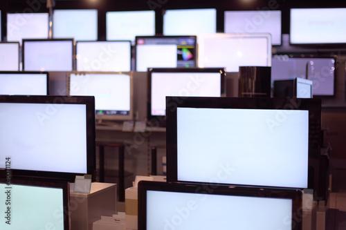 Rzędy telewizorów plazmowych z dużym przekątnym stoją na półkach w sklepie