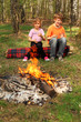 Two children sit near campfire and hold in their hands glasses