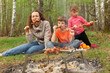 Mother and her children eat grilled shish kebab outdoor