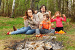 Mother, father and children eat grilled shish kebab outdoor