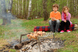 Two children sit near campfire with grill and barbecue