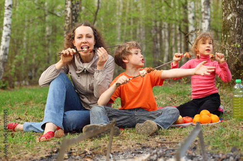 Mother and children finish to eat grilled shish kebab