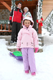 couple posing with daughter near chalet at ski resort