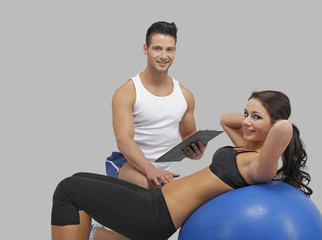 Handsome trainer with a women on fitness ball