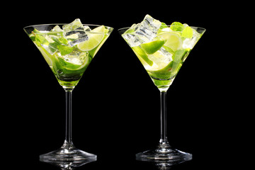 glasses of cocktails with lime and mint on black background